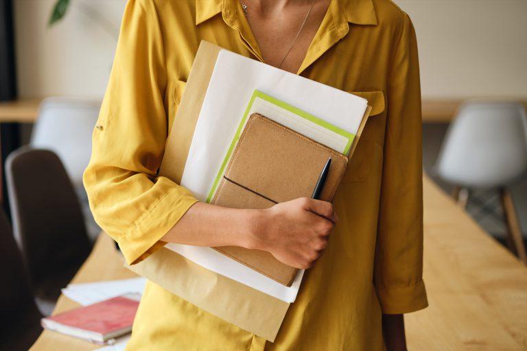 Kobieta trzyma notes i dziennik do edycji