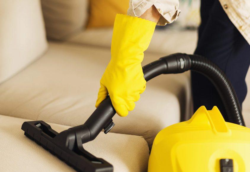 Odkurzanie sofy żółtym odkurzaczem