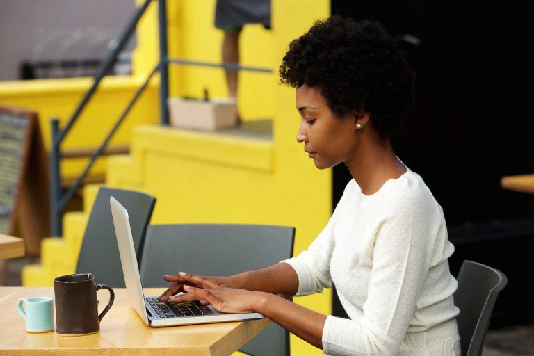 Kobieta pisze teksty na laptopie na swoją stronę www