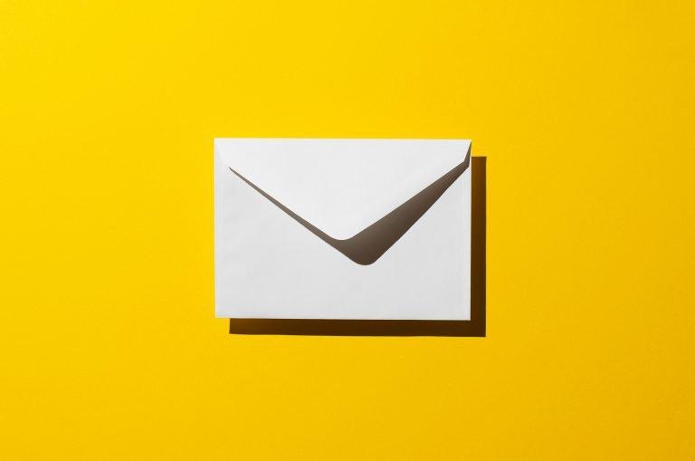 Koperta na żółtym tle - symbol poczty internetowej w cyber_Folks