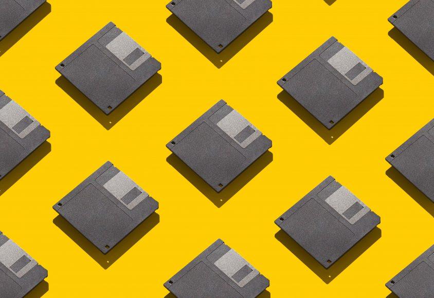 Grafika przedstawia kilkanaście dyskietek na żółtym tle