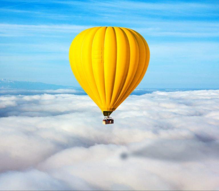 Żółty balon na tle pięknego niebieskiego nieba