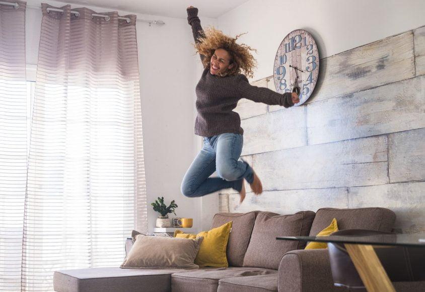 Rejestracja domeny - Kobieta skacząca po kanapie