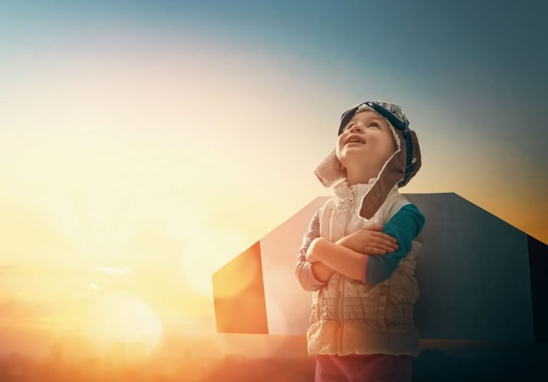 Dziecko w stroju pilota, wpatrzone w niebo