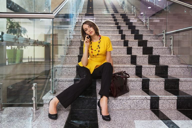 Kobieta siedząca na schodach i rozmawiająca przez telefon - jak zarejestrować domenę?