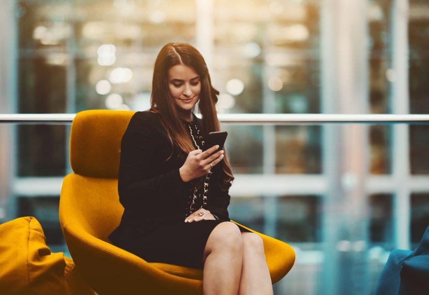 Kobieta siedząca na żółtym fotelu i rejestrująca domenę