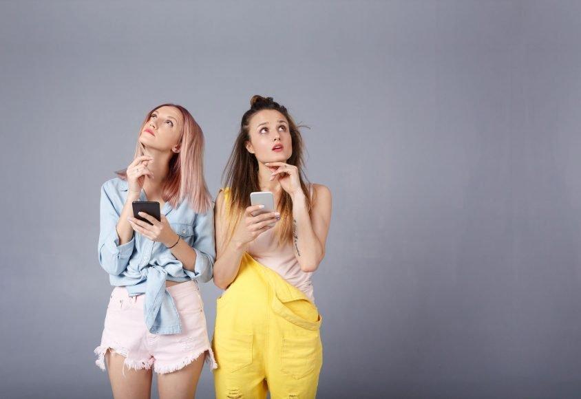 Dwie młode kobiety zastanawiające się jak zarejestrować domenę