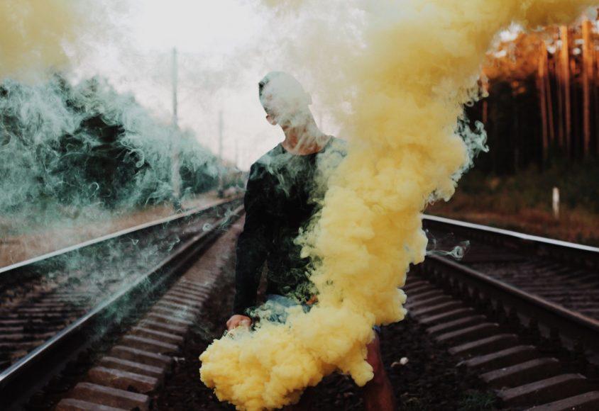Mężczyzna stojący na torach i trzymający racę dymną