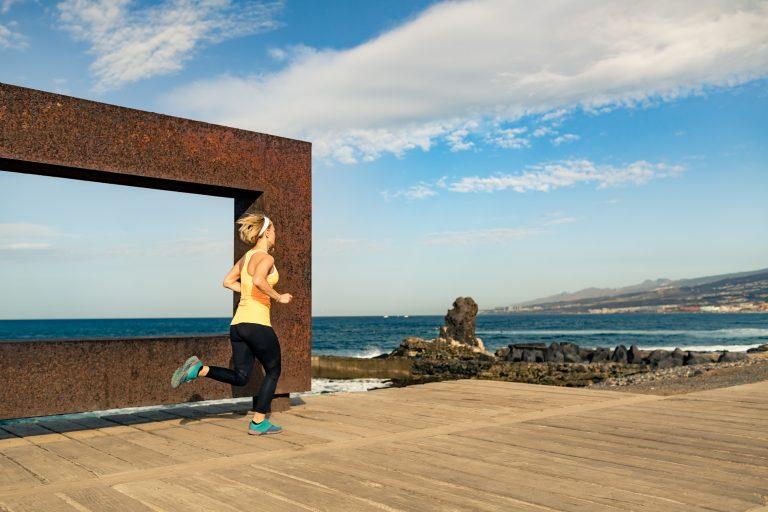 Kobieta biegnie energicznie promenadą nad brzegiem morza