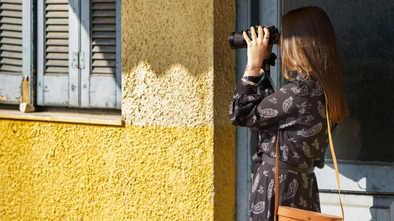 Opinie w sklepie internetowym - ich nie pozyskasz patrząc przez lornetkę. Pani przy żółtej ścianie patrzy przez lornetkę w dal.